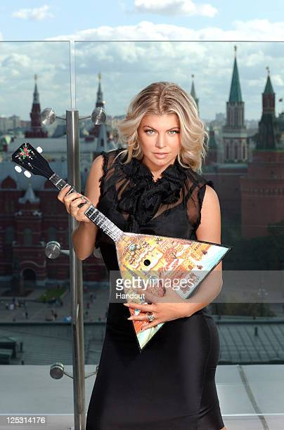 In this handout photo provided by Avon Fergie rocks out with the Balalaika the Russian national musical instrument at the launch of her new fragrance...