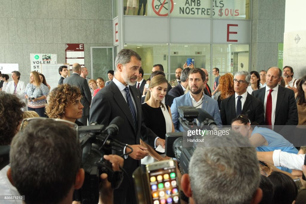 In this handout photo provided by Casa de S.M. el Rey de Espana, King Felipe VI of Spain and Queen Letizia of Spain speak to the media and meet with medical staff as they arrive to visit last Thursday's terrorist attack victims at the Hospital de la Santa Creu i Sant Pau on August 19, 2017 in Barcelona, Spain. Thirteen people were killed and dozens injured in the Las Ramblas area of Barcelona when a van hit crowds on August 17.