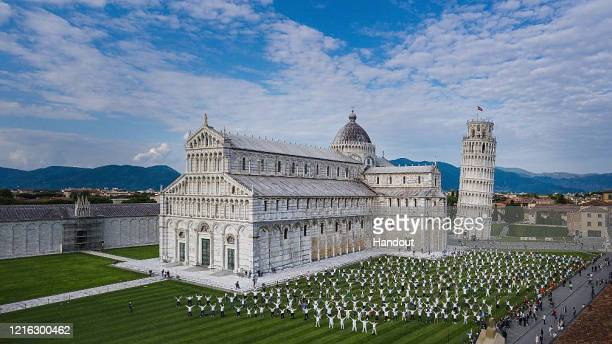 In this handout photo provided by Comune di Pisa, a view from a done shows people wearing face masks take part in a flash mob near the tower of Pisa...