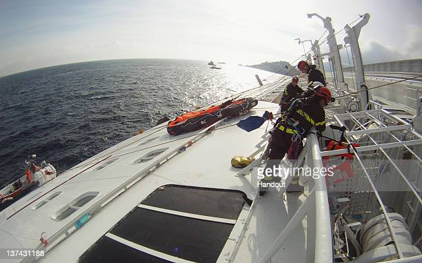 In this handout photo provided by Corpo Nazionale dei Vigili del Fuoco Firefighters work on the cruise ship Costa Concordia that lies grounded off...