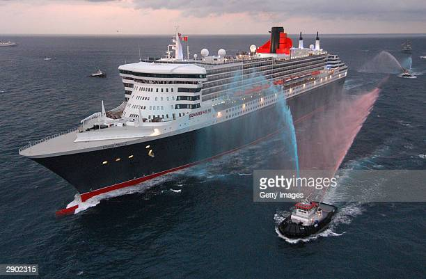 In this handout photo provided by Cunard Line, water-squirting tugboats salute the Queen Mary 2, the largest luxury ocean liner ever constructed, as...