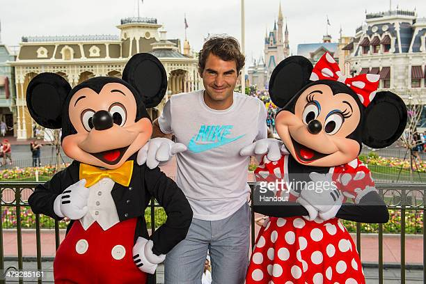 In this handout photo provided by Diseny Parks tennis legend Roger Federer poses with Mickey and Minnie Mouse at the Magic Kingdom park March 17 2014...
