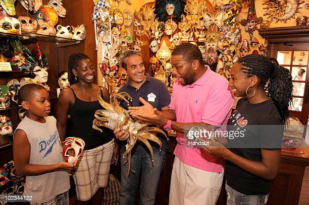 In this handout photo provided by Disney actor Anthony Anderson checks out handmade Venetian masks with Disney mask maker Giorgio Iurcotta at the...