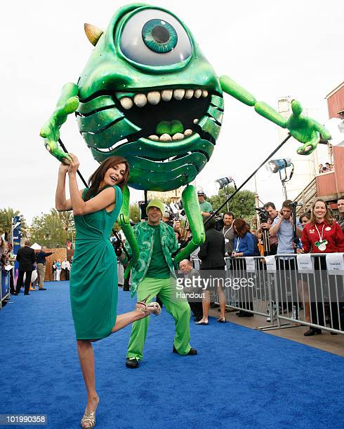 In this handout photo provided by Disney actress Teri Hatcher poses with a giant puppet of the DisneyPixar character Mike Wazowski as she arrives for...