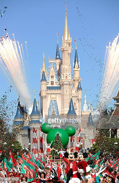 In this handout photo provided by Disney as fireworks explode above Cinderella Castle dancers and Disney characters perform while taping a segment of...