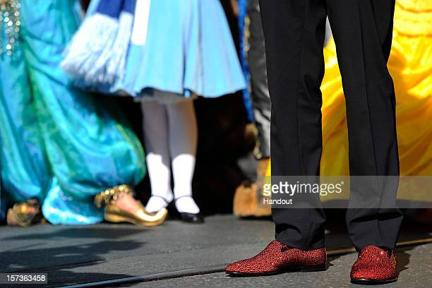 In this handout photo provided by Disney as he stands near Disney characters Princess Jasmine and Alice in Wonderland Nick Cannon's holiday shoes...