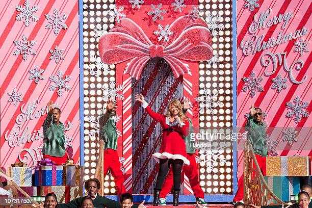 In this handout photo provided by Disney Grammy Awardwinning singer Mariah Carey waves to the crowd in front of an oversized Christmas card while...
