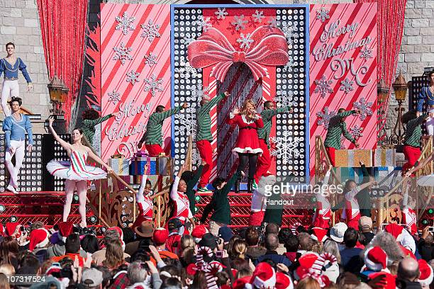In this handout photo provided by Disney Grammy Awardwinning singer Mariah Carey performs in front of an oversized Christmas card while taping the...