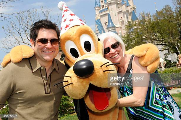In this handout photo provided by Disney Jay DeMarcus of the country music trio 'Rascal Flatts' and his mother Caron Myers pose with Pluto in front...