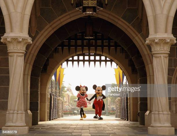 In this handout photo provided by Disney, Mickey and Minnie Mouse are seen walking through Sleeping Beauty Castle at the new Disneyland Park on...