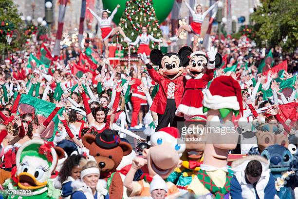 In this handout photo provided by Disney, Mickey and Minnie Mouse wave to the TV cameras amidst hundreds of dancers and Disney characters while...