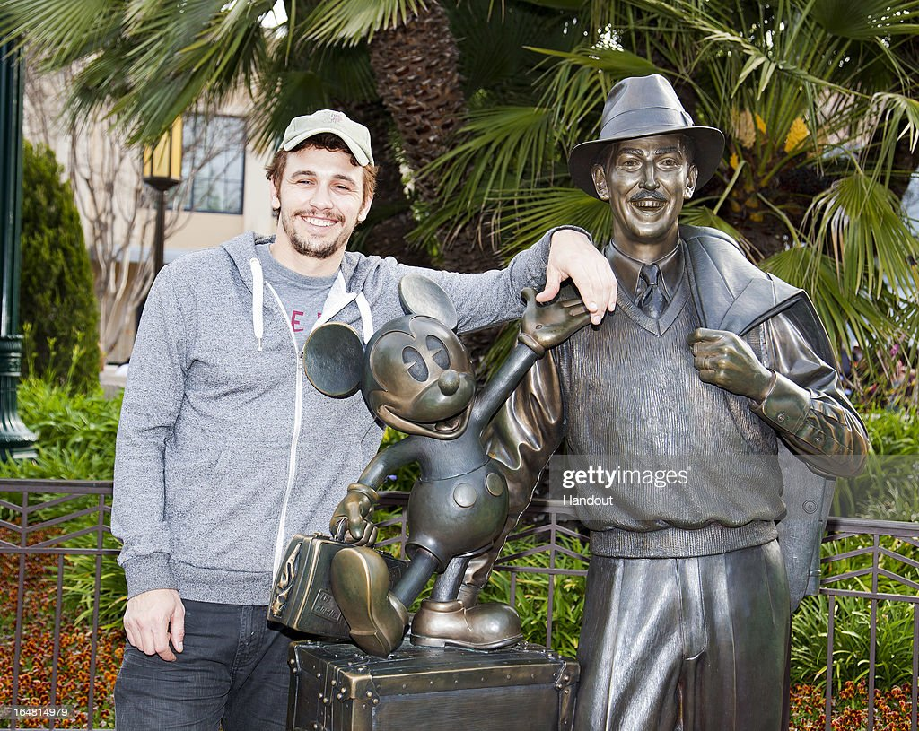 In this handout photo provided by Disney Parks, actor James Franco poses with a bronze statue of a young Walt Disney and his most famous creation, Mickey Mouse, called 'Storytellers' at Disney California Adventure park on March 28, 2013 in Anaheim, California. The statue reflects the optimistic outlook of Walt Disney upon his arrival in California in 1923 and is part of the Buena Vista Street area of the park which opened in 2012.