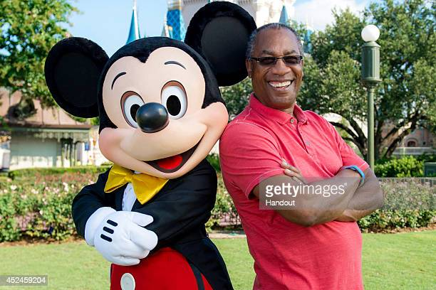 In this handout photo provided by Disney Parks actor Joe Morton of ABC series 'Scandal' poses with Mickey Mouse in the Magic Kingdom Park at the Walt...