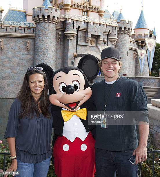 In this handout photo provided by Disney Parks actor Matt Damon and his wife Luciana pose with Mickey Mouse at Sleeping Beauty Castle at Disneyland...