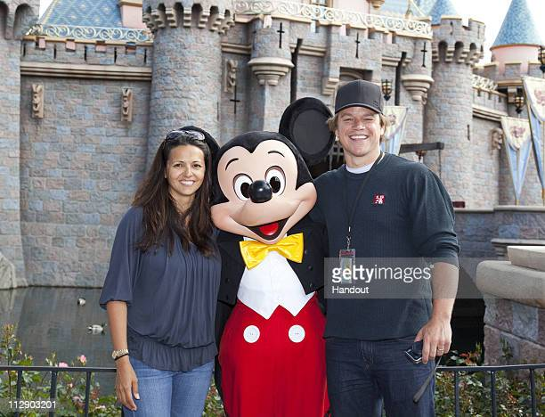 In this handout photo provided by Disney Parks, actor Matt Damon and his wife Luciana pose with Mickey Mouse at Sleeping Beauty Castle at Disneyland...