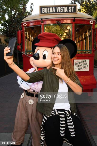 In this handout photo provided by Disney Parks Actress Jessica Alba takes a ride with Mickey Mouse on the Red Car Trolley at Disney California...