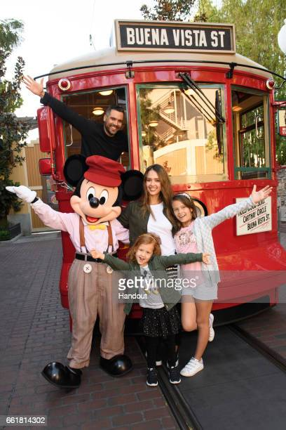 In this handout photo provided by Disney Parks, Actress Jessica Alba, husband Cash Warren and daughters Honor and Haven take a ride with Mickey Mouse...