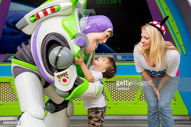 In this handout photo provided by Disney Parks, actress Melissa Joan Hart looks on as her son Tucker greets Buzz Lightyear at Magic Kingdom park on...