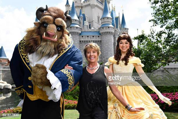 In this handout photo provided by Disney Parks actress singer artist and Disney Legend Paige O'Hara strikes a royal pose with Belle and Beast while...