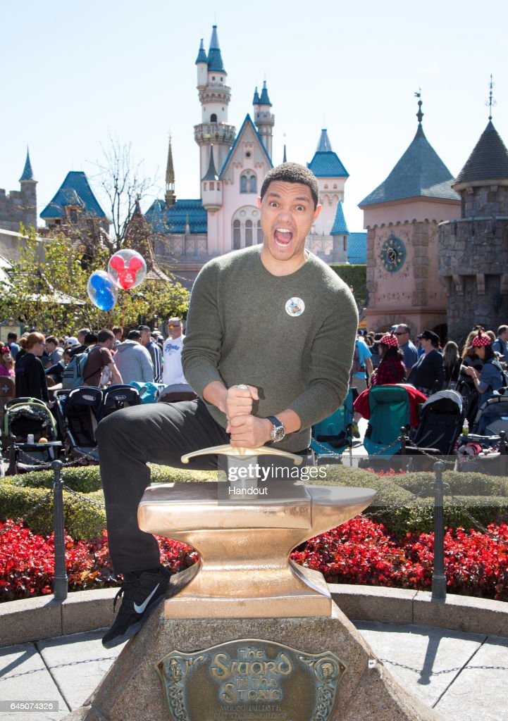 In this handout photo provided by Disney Parks, 'Daily Show' host Trevor Noah tries his luck at removing the Sword in the Stone in Fantasyland at Disneyland park February 24, 2017 in Anaheim, California.