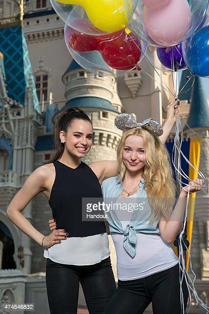 In this handout photo provided by Disney Parks Disney Channel's 'Descendants' stars Sofia Carson and Dove Cameron pose in front of the Cinderella...
