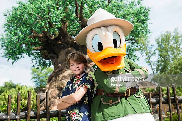In this handout photo provided by Disney Parks Disney's Pete's Dragon star Oakes Fegley poses with Donald Duck at Disney's Animal Kingdom on August 3...