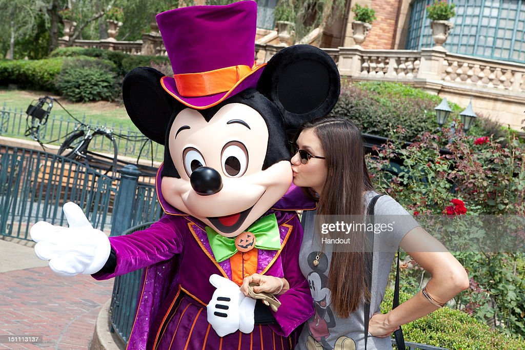 In this handout photo provided by Disney Parks, dressed for Halloween, Mickey Mouse gets a kiss from actress Nina Dobrev, star of The CW Network TV series 'The Vampire Diaries,' in front of The Haunted Mansion on September 1, 2012 at the Magic Kingdom park in Lake Buena Vista, Florida. Season four of 'The Vampire Diaries' premieres October 11, 2012.