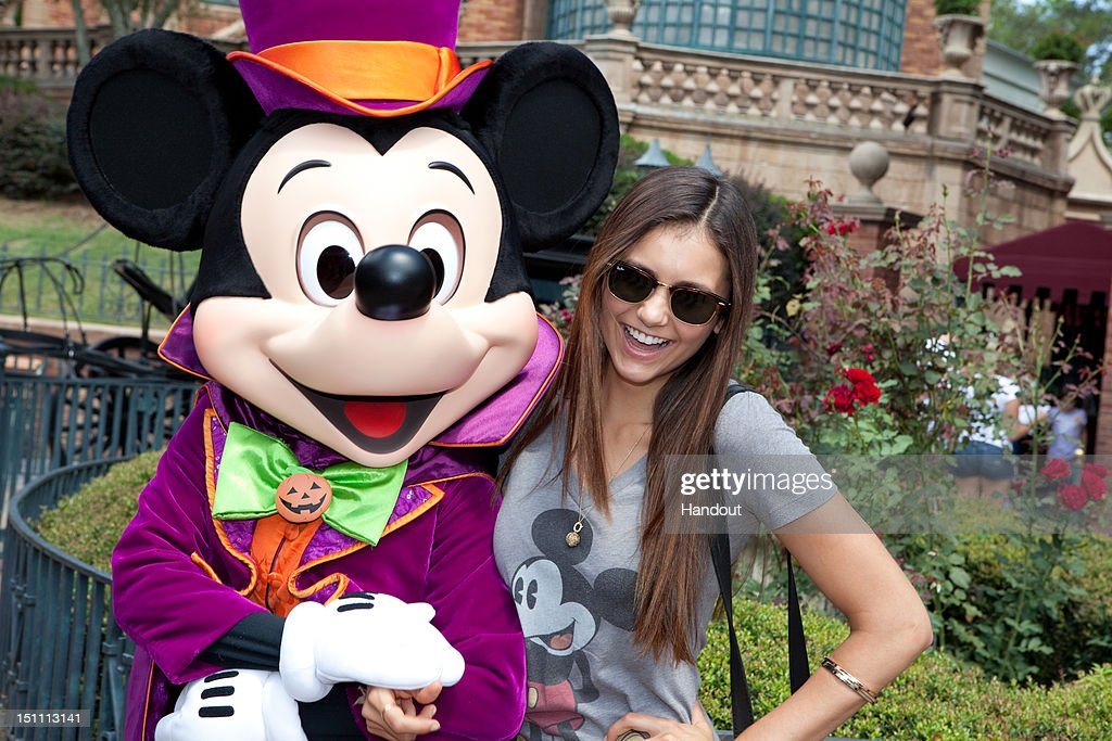 In this handout photo provided by Disney Parks, dressed for Halloween, Mickey Mouse poses with actress Nina Dobrev, star of The CW Network TV series 'The Vampire Diaries,' in front of The Haunted Mansion on September 1, 2012 at the Magic Kingdom park in Lake Buena Vista, Florida. Season four of 'The Vampire Diaries' premieres October 11, 2012.