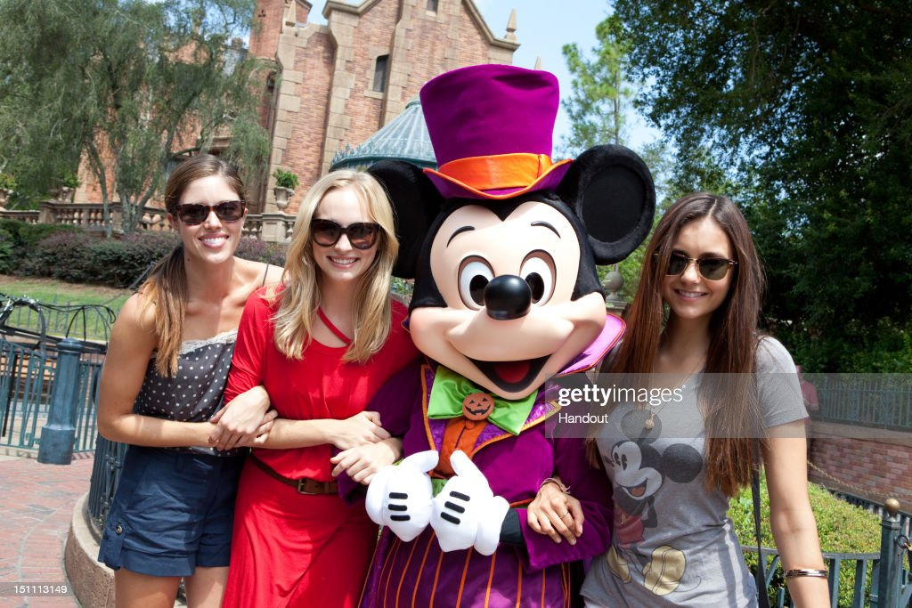 In this handout photo provided by Disney Parks, dressed for Halloween, Mickey Mouse poses with (L-R) actresses Kayla Ewell, Candice Accola and Nina Dobrev from The CW Network TV series 'The Vampire Diaries,' in front of The Haunted Mansion on September 1, 2012 at the Magic Kingdom park in Lake Buena Vista, Florida. Season four of 'The Vampire Diaries' premieres October 11, 2012.