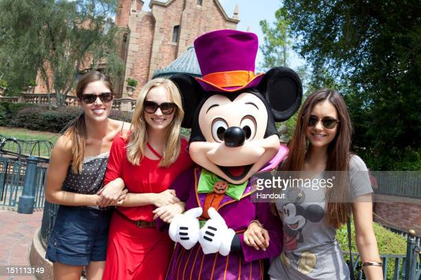 In this handout photo provided by Disney Parks, dressed for Halloween, Mickey Mouse poses with actresses Kayla Ewell, Candice Accola and Nina Dobrev...