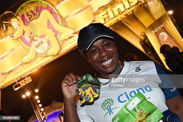 In this handout photo provided by Disney Parks Emmy Awardwinning actress Uzo Aduba proudly showcases her participation medal after completing the...