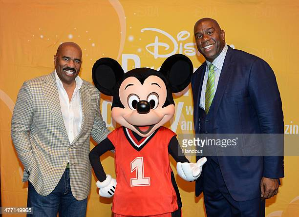 In this handout photo provided by Disney Parks entertainer Steve Harvey and NBA Hall of Fame member Magic Johnson pose with Mickey Mouse during the...