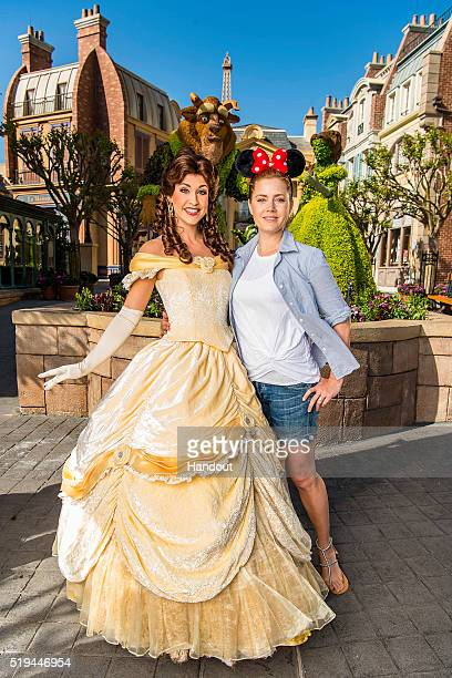 In this handout photo provided by Disney Parks fivetime academyawardnominated actress Amy Adams poses with princess Belle at the Epcot International...