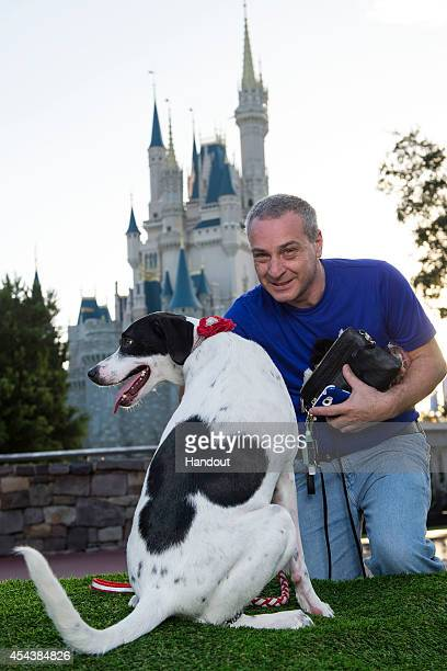 In this handout photo provided by Disney Parks Francisco Aguerre and his dog 'Lily' pose at the Magic Kingdom at Walt Disney World Resort August 30...