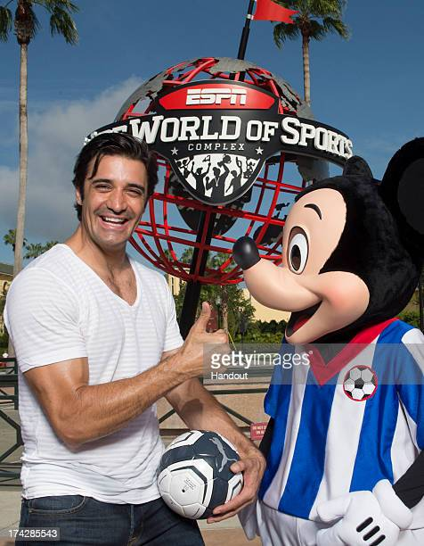 In this handout photo provided by Disney Parks, French-born model and actor Gilles Marini poses with Mickey Mouse at ESPN Wide World of Sports at...