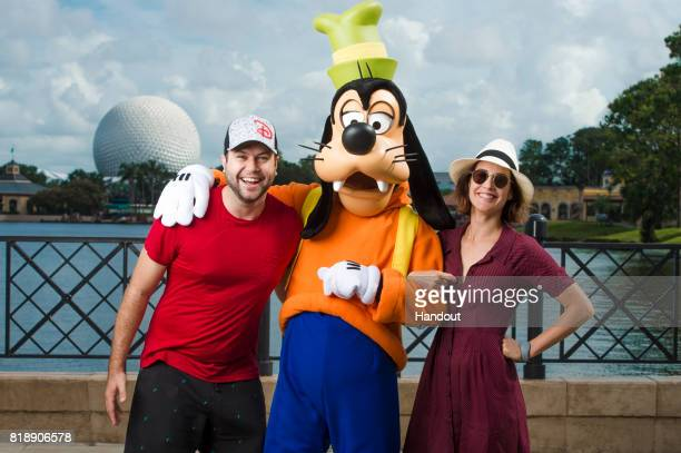 In this handout photo provided by Disney Parks, Hollywood couple Taran Killam and Cobie Smulders pose with their favorite Disney pal, Goofy, on July...