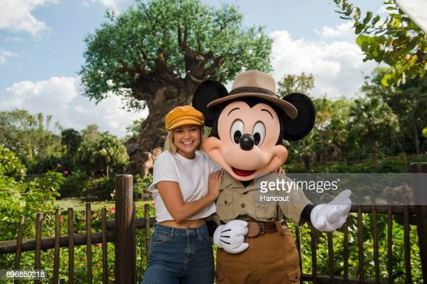 In this handout photo provided by Disney Parks Hollywood Records artist and actress Olivia Holt poses with Mickey Mouse at Disney's Animal Kingdom on...