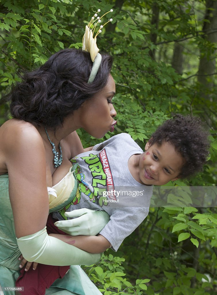 In this handout photo provided by Disney Parks, in this photo taken May 29, 2013 Jennifer Hudson, in costume as Tiana from Disney's 'The Princess and the Frog,' shares a playful moment with her son, David, while on a break during a photo shoot with acclaimed photographer Annie Leibovitz in Patterson, New York. The newest 'Disney Dream Portrait' was commissioned by Disney Parks for their ongoing celebrity advertising campaign which debuted in 2007. The Leibovitz image, which will appear in upcoming issues of Vanity Fair, O - The Oprah Magazine, and People is entitled, 'Where you always follow your heart.' Behind the scenes with Jennifer Hudson as Tiana.