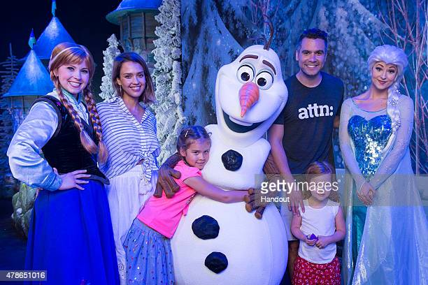 In this handout photo provided by Disney Parks Jessica Alba and husband Cash Warren along with daughters Honor and Haven pose with Anna Olaf and Elsa...