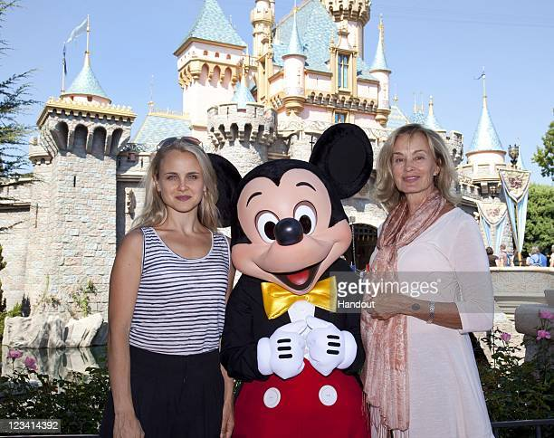In this handout photo provided by Disney Parks Jessica Lange and daughter Shura pose with Mickey Mouse outside Sleeping Beauty Castle at Disneyland...