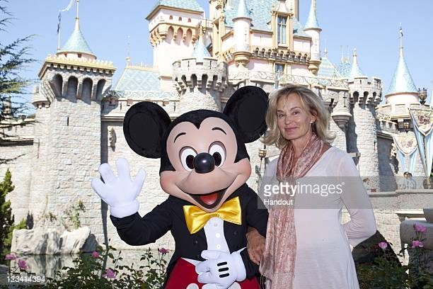 In this handout photo provided by Disney Parks Jessica Lange poses with Mickey Mouse outside Sleeping Beauty Castle at Disneyland On September 2 2011...