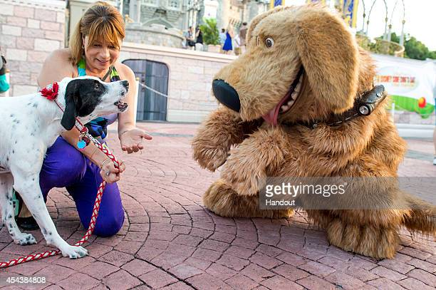 In this handout photo provided by Disney Parks Mejay Aguerre and her dog Lily meet the DisneyPixar canine character Dug at the Magic Kingdom at Walt...