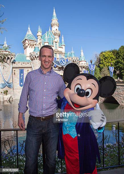 In this handout photo provided by Disney Parks Mickey Mouse greets Denver Broncos quarterback Peyton Manning at Sleeping Beauty Castle at Disneyland...