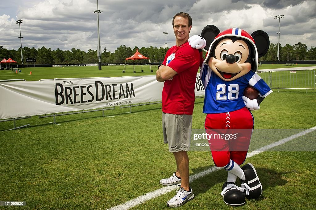 In this handout photo provided by Disney Parks, New Orleans Saints All-Pro quarterback Drew Brees poses with Mickey Mouse at ESPN Wide World of Sports Complex at Walt Disney World on June 26, 2013 in Lake Buena Vista, Florida. Brees is at the Disney sports complex to conduct his Drew Brees Passing Academy. The three-day Drew Brees Passing Academy and 7-on-7 Tournament includes top high school football players from across the country competing June 27-29 at Walt Disney World Resort. Brees, a former Super Bowl MVP, will be joined at his passing academy by Saints teammates Jonathan Vilma and Jimmy Graham. Proceeds from the academy benefit the Brees Dream Foundation, established in 2003 by Brittany and Drew Brees to help improve the quality of life for cancer patients and provide care, education and opportunities for children and families in need.