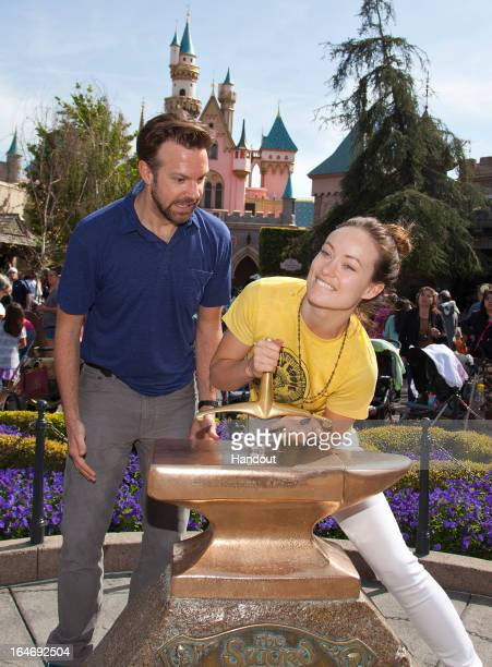 In this handout photo provided by Disney Parks Newlyengaged couple Jason Sudeikis and Olivia Wilde try their luck at removing the 'Sword in the...