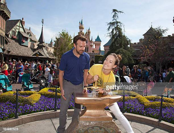 In this handout photo provided by Disney Parks Newlyengaged couple Jason Sudeikis and Olivia Wilde try their luck at removing the Sword in the Stone...