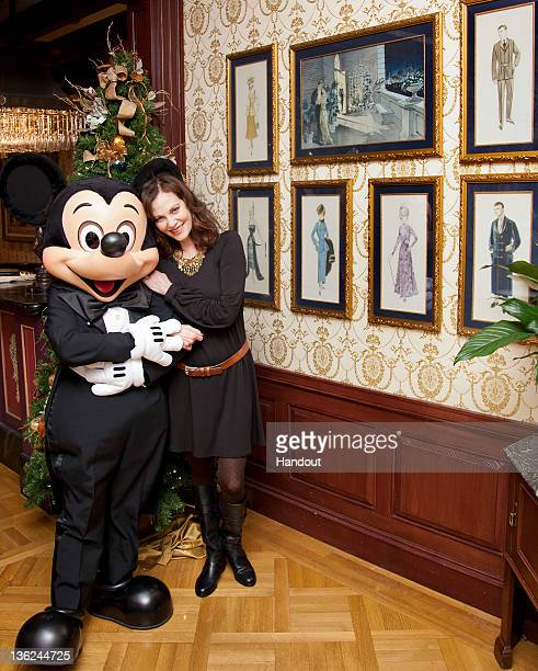 In this handout photo provided by Disney Parks, Oscar-nominated actress Lesley Ann Warren poses with Mickey Mouse beside original costume sketches...