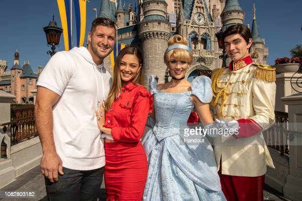 In this handout photo provided by Disney Parks professional athlete and sports analyst Tim Tebow and fiancée DemiLeigh NelPeters take flight on Dumbo...