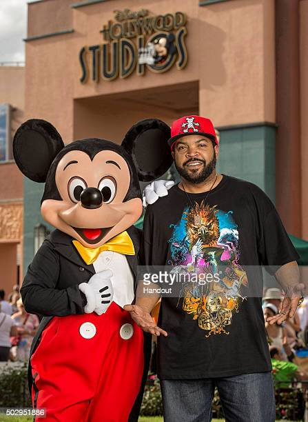 In this handout photo provided by Disney Parks rapper actor and filmmaker Ice Cube kicks back with Mickey Mouse while vacationing with his family...