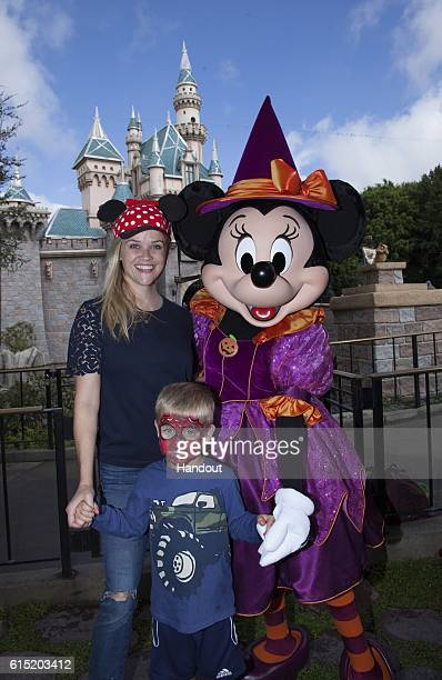 In this handout photo provided by Disney Parks Reese Witherspoon and her son Tennessee age 4 celebrate Halloween Time with Minnie Mouse outside...